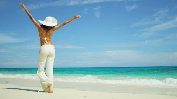 Young Latin American girl in trousers and sunhat barefoot on tropical beach Royalty-free stock video