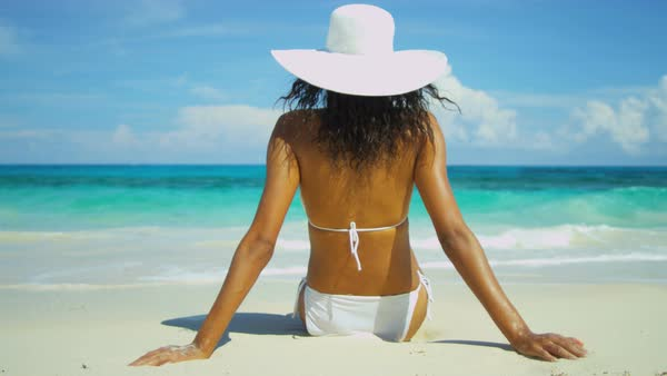 Latin American girl in a bikini and sunhat sunbathing by a tropical ocean  Royalty-free stock video