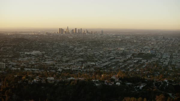 Aerial view of urban Los Angeles with distant skyscrapers at sunrise Royalty-free stock video
