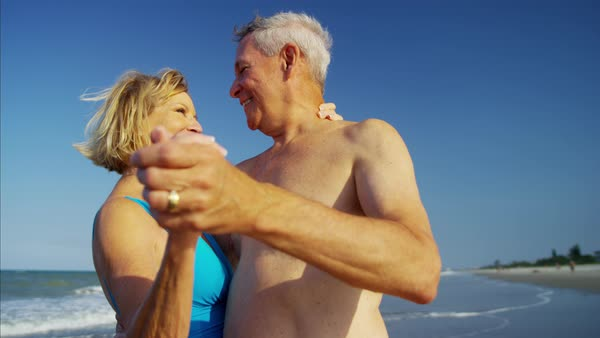 Happy mature couple in swimsuits dancing on the beach vacation Royalty-free stock video