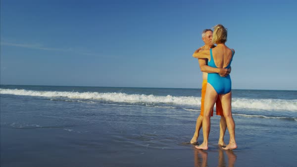 Happy mature couple in swimsuits dancing on the beach Royalty-free stock video
