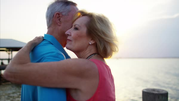 Mature couple in colorful clothing having fun on the beach at sunrise Royalty-free stock video