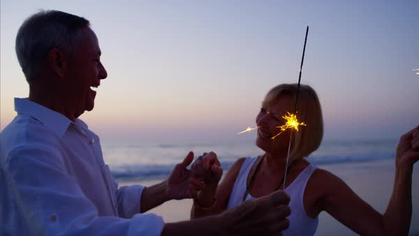 Mature Caucasian couple enjoying beach party with sparklers at sunset Royalty-free stock video