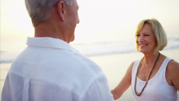 Mature Caucasian couple in white clothing dancing together on the ocean beach Royalty-free stock video