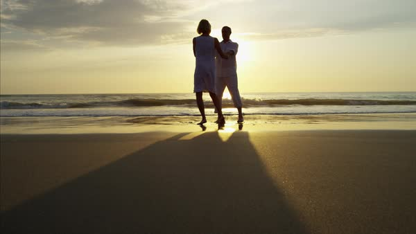 Silhouette of mature Caucasian couple dancing on the ocean beach at sunrise Royalty-free stock video