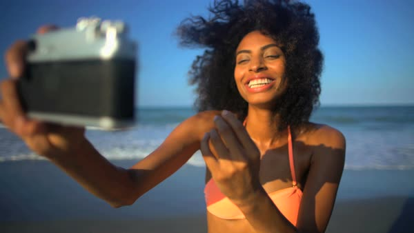 536c888f60560 Young smiling African American female in swimwear having fun taking selfie  on her beach holiday Royalty