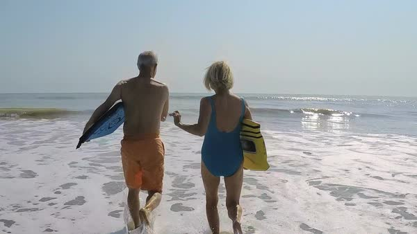 Fit healthy mature Caucasian couple in swimsuits running with bodyboards on their beach vacation Royalty-free stock video