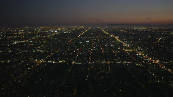 Aerial cityscape view of vehicle traffic showing grid system in illuminated city suburbs at dusk America Los Angeles California USA Royalty-free stock video