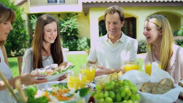 Summer living of young European family dining outdoors on healthy salad and organic fruit juice Royalty-free stock video