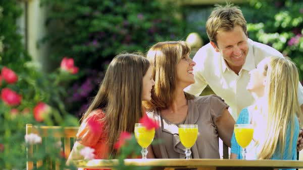 Attractive Caucasian couple and teenage daughters enjoying family time together outdoors drinking healthy fresh orange juice Royalty-free stock video