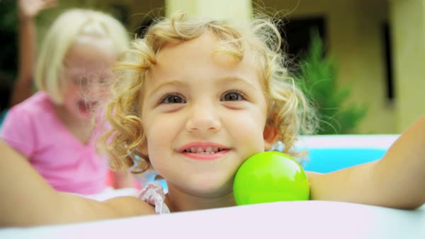 Portrait of happy cute Caucasian American kid having fun with her friends in coloured ball pool  Royalty-free stock video