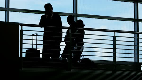 Silhouette of Caucasian American male business manager in modern airport building atrium using mobile technology  Royalty-free stock video