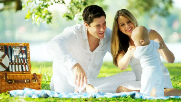 Loving happy Caucasian father and mother chilling outdoors on the blanket holding their young child in the park Royalty-free stock video