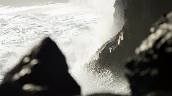 Steam rising as crashing ocean waves hit molten lava falling into coastal waters slow motion Royalty-free stock video