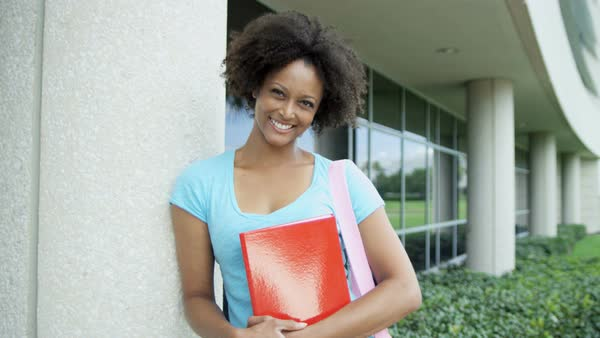 Portrait of young woman carrying library books at front of modern college campus Royalty-free stock video