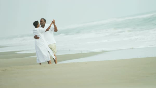 Laughing retired senior African American couple having fun together dancing on the beach enjoying the outdoor lifestyle Royalty-free stock video