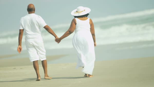 Companionable elderly African American couple holding hands outdoors walking along the beach enjoying leisure Royalty-free stock video