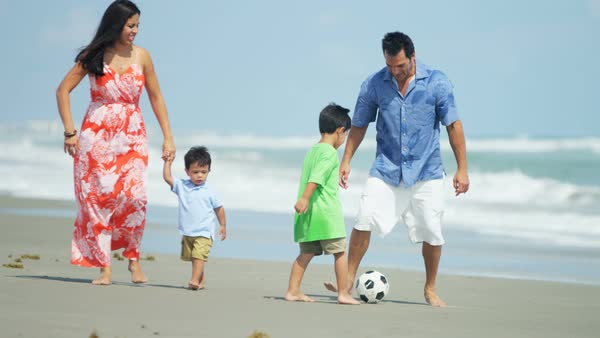 Hispanic father playing soccer on the beach with his son and walking along with his family Royalty-free stock video