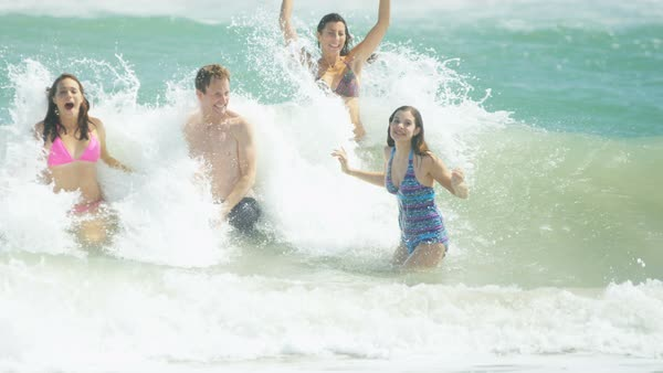 A healthy Caucasian family having fun in the ocean splashing and catching the waves Royalty-free stock video