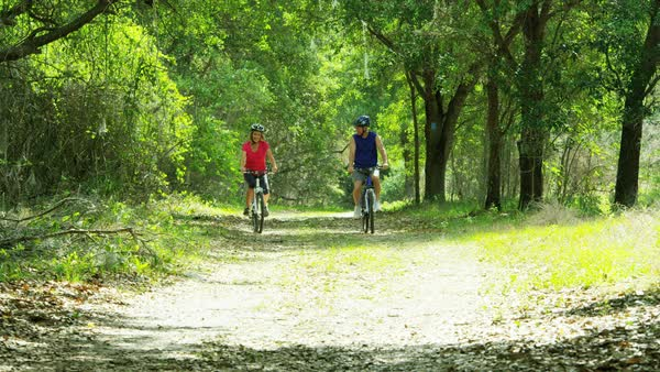 Mature Caucasian American couple enjoying biking outdoor in the forest  Royalty-free stock video