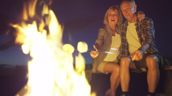 Healthy senior Caucasian American couple toasting marshmallows over a campfire in the camp in the evening outdoors Royalty-free stock video