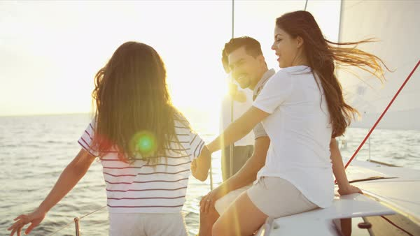 Young Hispanic family enjoying carefree lifestyle on vacation sailing the ocean on luxury yacht sun flare Royalty-free stock video