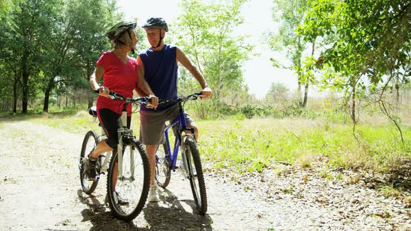 Active senior Caucasian American couple enjoying their outdoor lifestyle cycling in the forest Royalty-free stock video