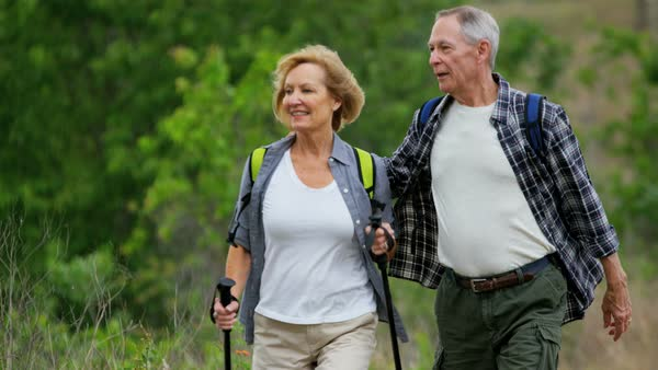 Healthy retired Caucasian American couple enjoying their vacation hiking to keep fit in the countryside Royalty-free stock video