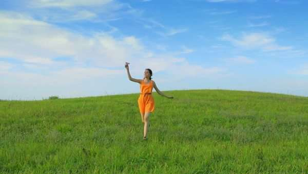 Happy young girl holding a paper plane and running, childhood, camera movement Royalty-free stock video