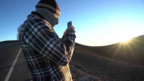 Medium shot of a man taking pictures at the Mauna Kea Observatories in Hawaii Royalty-free stock video