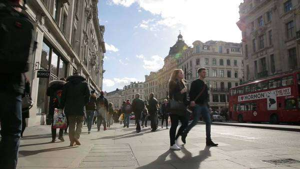 London, United Kingdom – February 21, 2014: Pedestrians walk on Regent Street on in London, UK. Regent Street is the main shopping street of London. Royalty-free stock video
