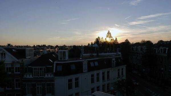 Timelapse of urban scene in Amsterdam with a sunset over the rooftops of Amsterdam suburbs Royalty-free stock video