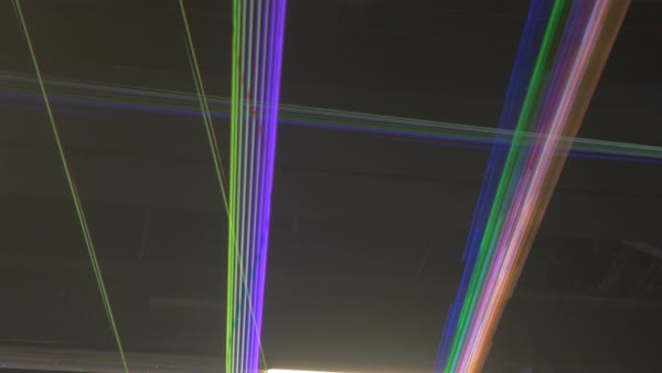 Thin different colored streaks of laser lights expand and collapse while criss-crossing each other.  Royalty-free stock video