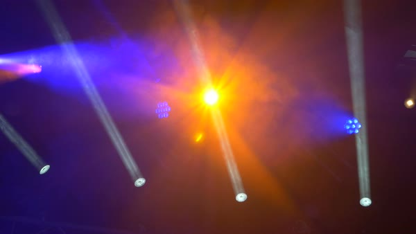 An orange colored stage light shining directly at the camera from above. Beam lights projecting underneath.  Royalty-free stock video