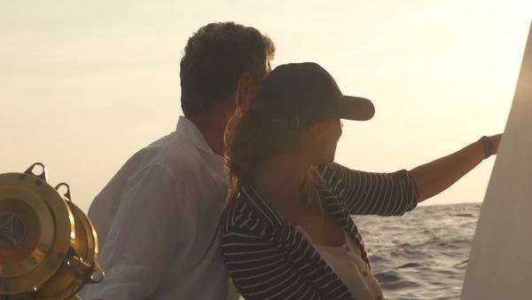 Slow motion of man and woman watch setting sun from big game fishing boat Royalty-free stock video