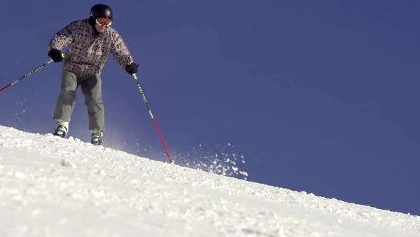 Beautiful slow motion of skier carving down the ski track fast with snow spraying behind him Royalty-free stock video