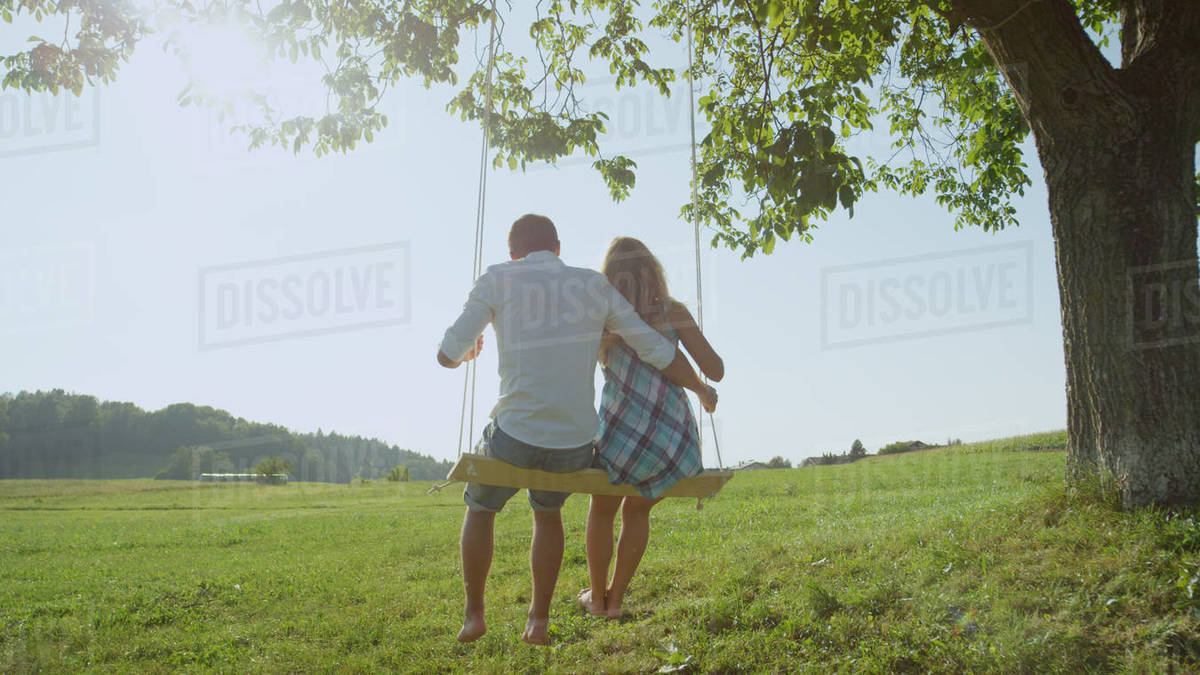 Unrecognizable young couple swaying on a swing under green tree observing the romantic spring afternoon. Man and woman in love enjoying peaceful view of summer day gazing into distance. Royalty-free stock photo