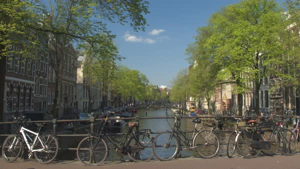 AMSTERDAM, NETHERLANDS - 7th MAY 2016: Antique bicycles locked on bridge, people enjoying sunny afternoon hanging on riverbank, relaxing and sightseeing. Small cruising boats anchored in river canals Royalty-free stock video