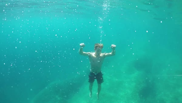 SLOW MOTION, CLOSE UP, UNDERWATER: Young man drowning in deep ocean, sinking to the rocky ocean bottom. Air bubbles leaving victim's mouth. Unexperienced bad swimmer facing terrible and painful death  Royalty-free stock video