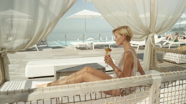 SLOW MOTION, CLOSE UP: Smiling healthy young Caucasian woman lying on daybed in the shade, hiding from sun and drinking refreshing cocktail in luxurious hotel beach bar overlooking amazing blue ocean Royalty-free stock video