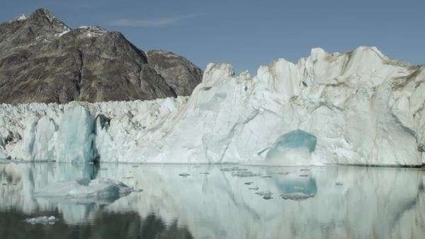 Locked off shot capturing a mass of ice detaching from an iceberg and falling into water Rights-managed stock video
