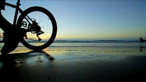 Tilting shot showing the wheels of a bicycle moving on wet sand reflecting the sky Rights-managed stock video