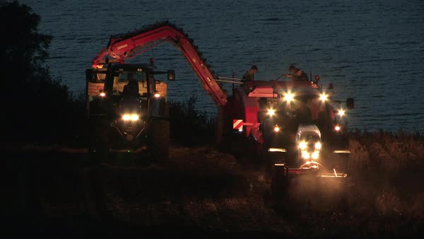 Wide-angle of a tractor harvesting at night Rights-managed stock video