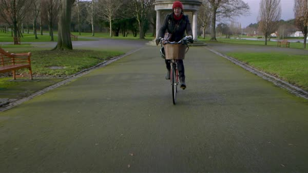 Wide shot of a woman biking in a park Rights-managed stock video