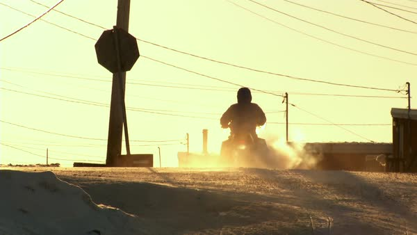 Tracking shot of a man riding a snowmobile at sunset Rights-managed stock video