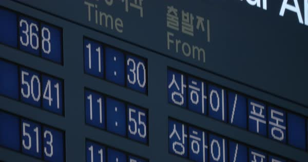 Close-up tilt shot of international arrivals on flight schedule with information on Korean and English languages Royalty-free stock video
