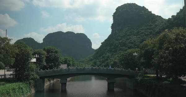 Cinemagraph - Man walking across the bridge in Trang An, Scenic Landscape Complex in Vietnam Royalty-free stock video