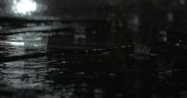 Rain drops falling into the puddle on sidewalk by the road at night Royalty-free stock video
