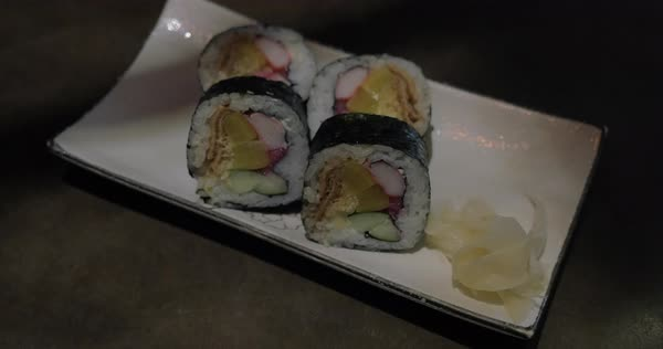 Close-up shot of waitress serving a portion of sushi rolls with ginger spice and placing chopsticks on the plate Royalty-free stock video