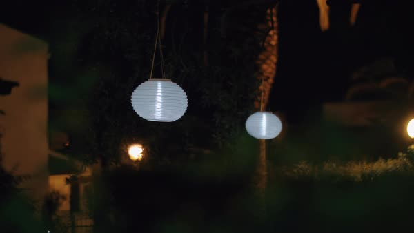 House Garden At Night With White Chinese Paper Lanterns Hanging In The Trees And Illuminating Darkness